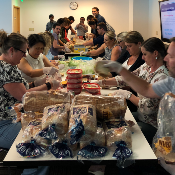 Employees make lunches for distribution to a youth program in South Seattle with #HashtagLunchbag.